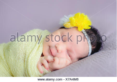 Portrait of a smiling baby girl sleeping - Stock Photo