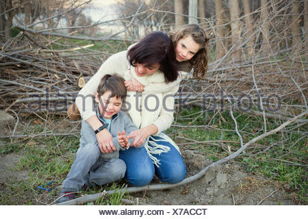 Mother and two children sitting in the forest - Stock Photo