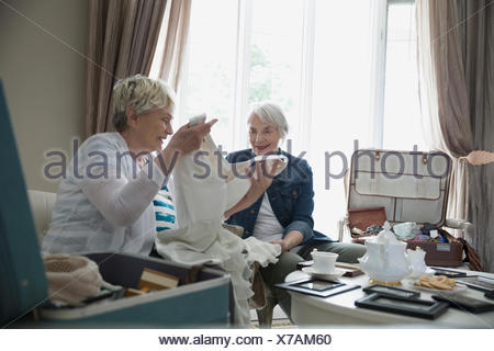 Senior women drinking tea and looking at old wedding dress - Stock Photo