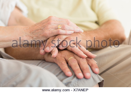 Senior couple sitting on couch holding hands - Stock Photo