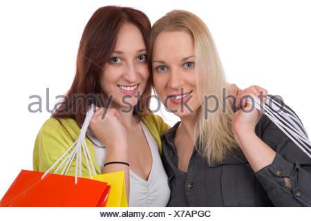 Zwei Freundinnen haben Spaß beim Einkaufen, isoliert vor einem weissen Hintergrund - Stock Photo
