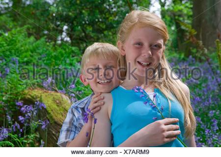 Children sitting on log among bluebell flowers - Stock Photo