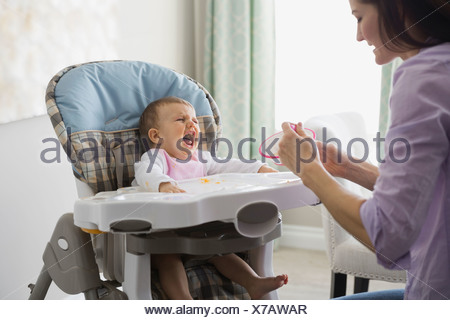 Mother feeding crying baby at home - Stock Photo