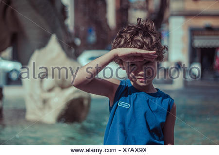 Boy looking at view with hand raised to forehead, shielding eyes - Stock Photo