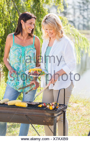 Two Women Cooking Barbeque In Countryside - Stock Photo