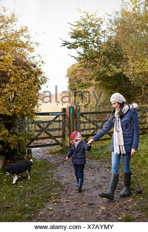 Mother And Daughter Taking Dog For Walk In Fall Landscape - Stock Photo