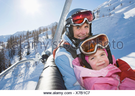Young girl and grandmother on chair lift - Stock Photo