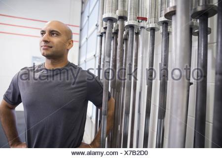 Man standing beside barbell rack - Stock Photo