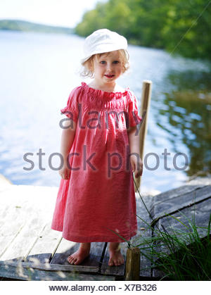 A girl in red dress standing on a plank, Sweden. - Stock Photo