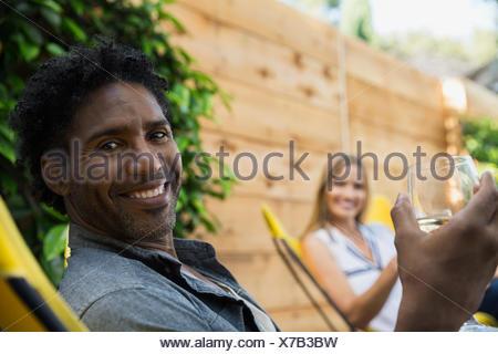 Portrait smiling man drinking wine on patio - Stock Photo