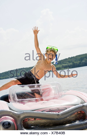A young boy standing in an inflatable raft on a lake - Stock Photo