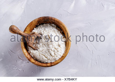Olive wood bowl with wheat flour and scoop for home baking. Over gray concrete background. Top view, copy space - Stock Photo