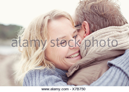 Happy woman embracing man outdoors - Stock Photo