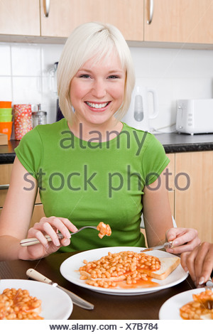 Young woman eating beans on toast - Stock Photo