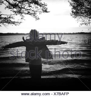 Rear View Of Woman Enjoying Wind At Shore - Stock Photo