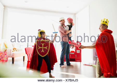 Father and daughter in costumes playing sword fight - Stock Photo