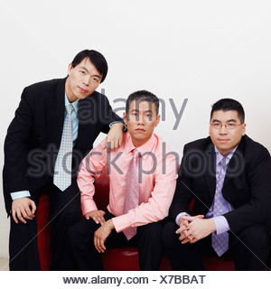 Portrait of four businessmen sitting together on a couch - Stock Photo