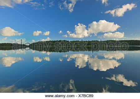 Cumulus clouds reflected in Lac Seul Ear Falls Ontario Canada - Stock Photo