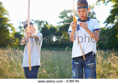 Two young boys holding bow and arrow - Stock Photo