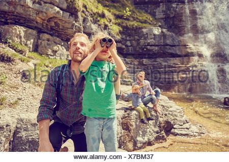 Young family exploring beside waterfall - Stock Photo