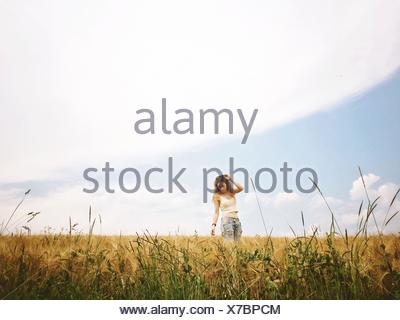 Young Woman Standing On Wheat Field - Stock Photo