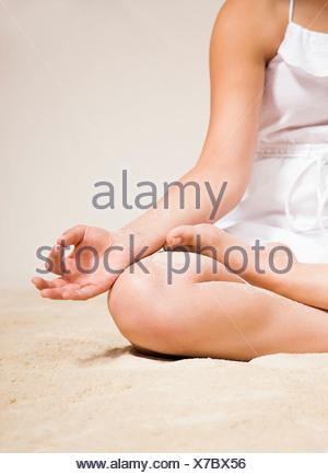 USA, Illinois, Metamora, Young woman doing yoga on beach - Stock Photo