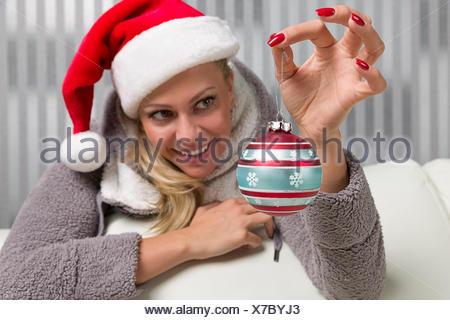 Frau mit Weihnachtsmütze hält eine Christbaumkugel und denkt schon freudig an Weihnachten - Stock Photo