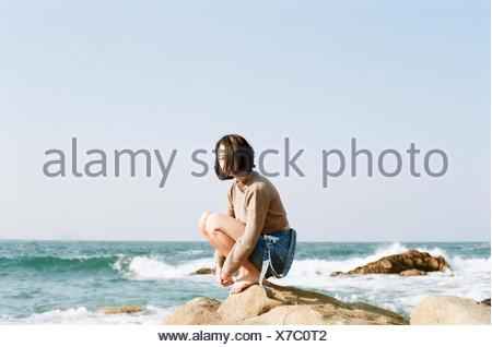 Side View Of A Woman Sitting On Beach - Stock Photo