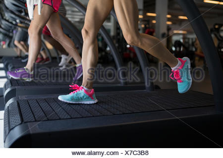 Legs of women running on treadmills at gym - Stock Photo