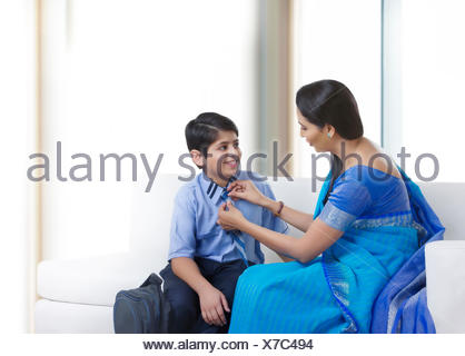 Mother helping son with neck tie - Stock Photo