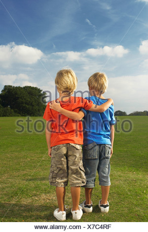 boys with arms around each other - Stock Photo