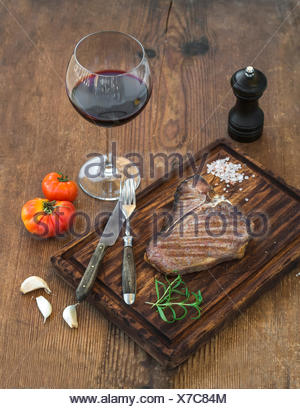 Cooked meat t-bone steak on serving board with garlic cloves, tomatoes, rosemary, spices and glass of red wine over rustic woode - Stock Photo
