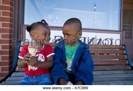 Boy and girl disagreeing over ice cream cone - Stock Photo