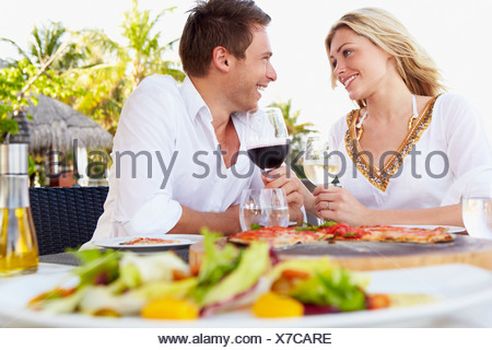 Couple Enjoying Meal In Outdoor Restaurant - Stock Photo