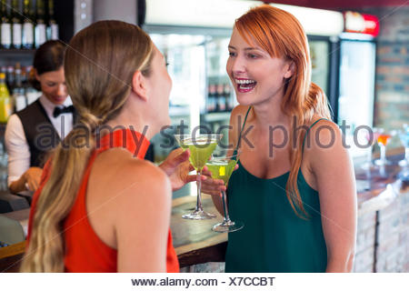 Happy friends holding a cocktail in front of bar counter - Stock Photo