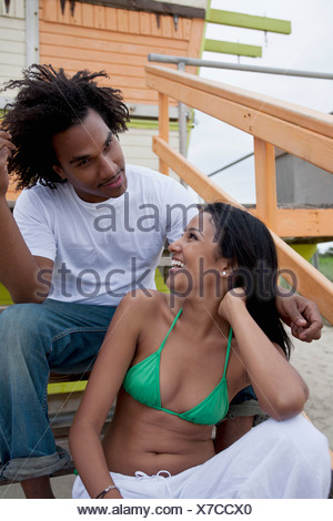A young couple sitting on steps at the beach - Stock Photo