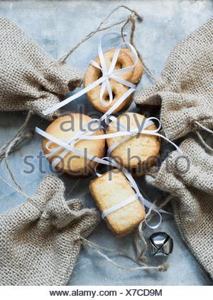 Overhead view of shortbread cookies tied with white ribbon and burlap bags - Stock Photo