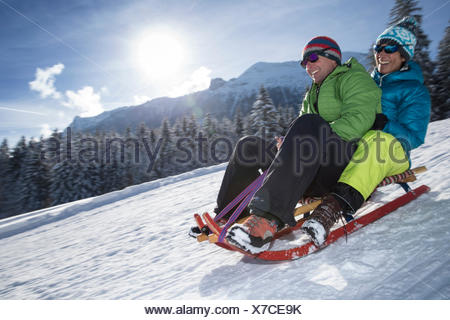 Germany, Bavaria, Inzell, couple having fun on a sledge in snow-covered landscape - Stock Photo
