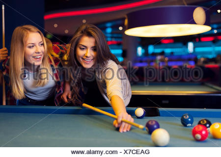 Friends hanging out at the pool table - Stock Photo