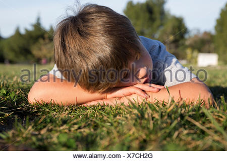 Sullen boy with head down lying on park grass - Stock Photo