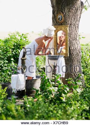 Woman taking a bath in a garden, Sweden. - Stock Photo