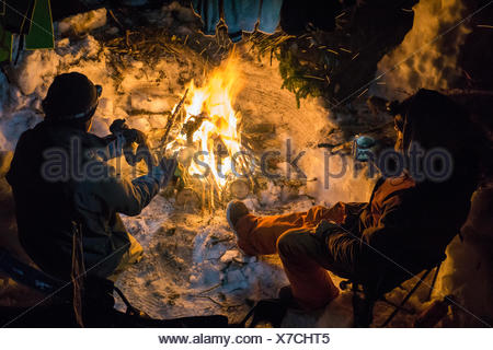 Snowboarding warming up drinking tea around fire at night - Stock Photo