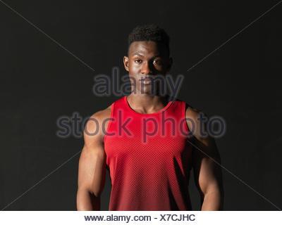 Portrait of athlete, black background - Stock Photo