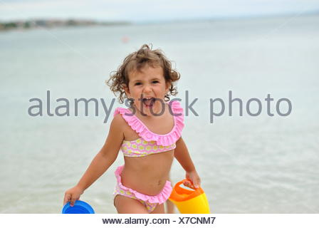 Girl in pink bikini playing on the beach - Stock Photo