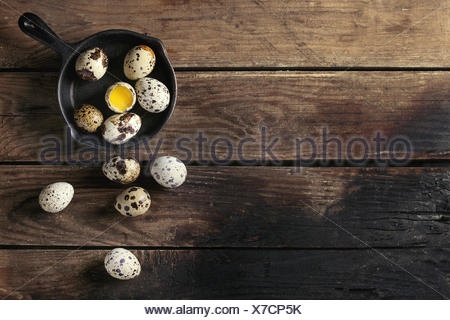 Whole and broken quail eggs with yolk in shell in small iron cast pan over old wooden plank background. Top view with space - Stock Photo