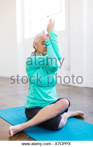 Senior woman practicing yoga on mat - Stock Photo