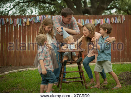 Family celebrating baby boys' first birthday in back yard - Stock Photo