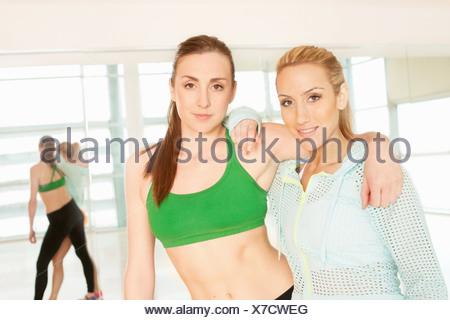 Women standing in gymnasium with arm around - Stock Photo