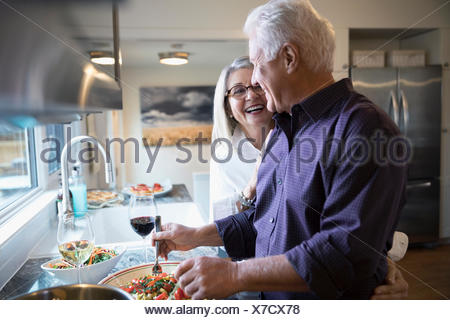 Affectionate senior couple laughing cooking and drinking wine in kitchen - Stock Photo