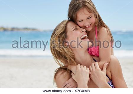 MODEL RELEASED. Mother carrying daughter on her back. - Stock Photo